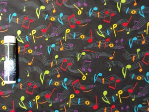 fabric with rainbow-colored music notes on a black background