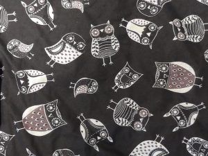 fabric with white and brown owls on a black background