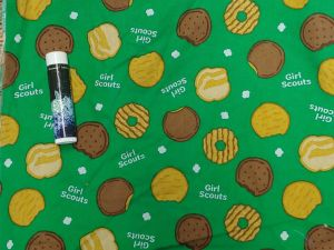 various girl scount cookies on a green background with th words Girl Scouts in white