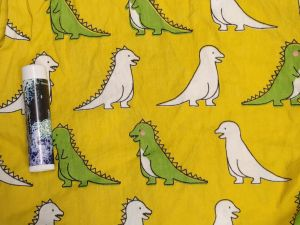 green and white Godzillas spaced on a mustard background