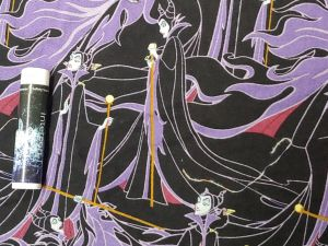 Maleficent in black and purple with her staff