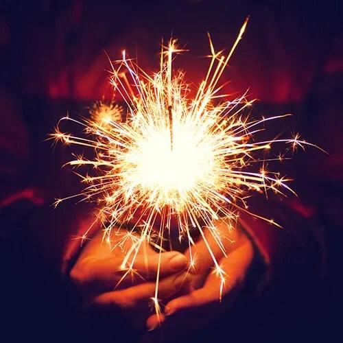Hands holding a lit sparkler on bonfire night