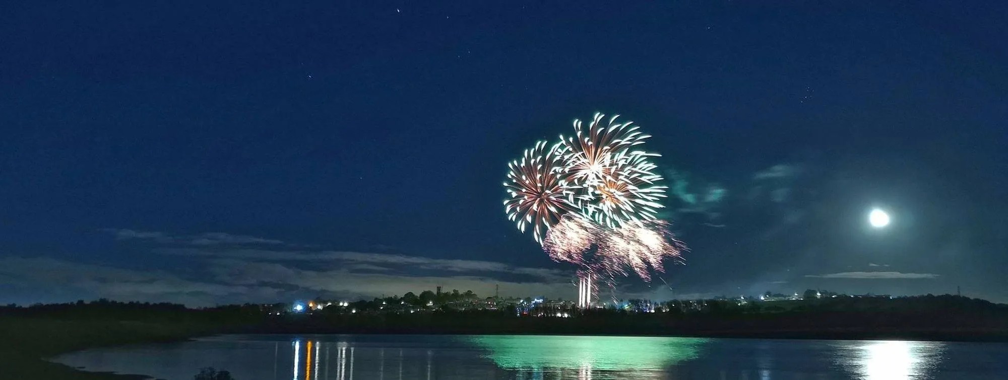Professional firework display reflected in a lake