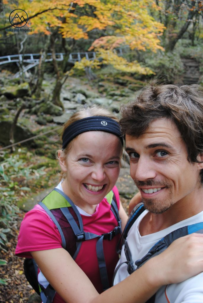 An image of the author and her husband standing in a forest in Hallasan National Park. Behind them is a forest full of fall colors, a trail and a dry, rocky stream bed.