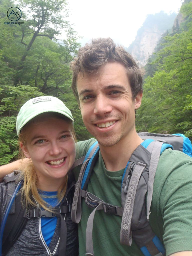 An image of the author and her husband in Seoraksan National Park. The two are wearing backpacks, and smiling at the camera in front of a forest of green.