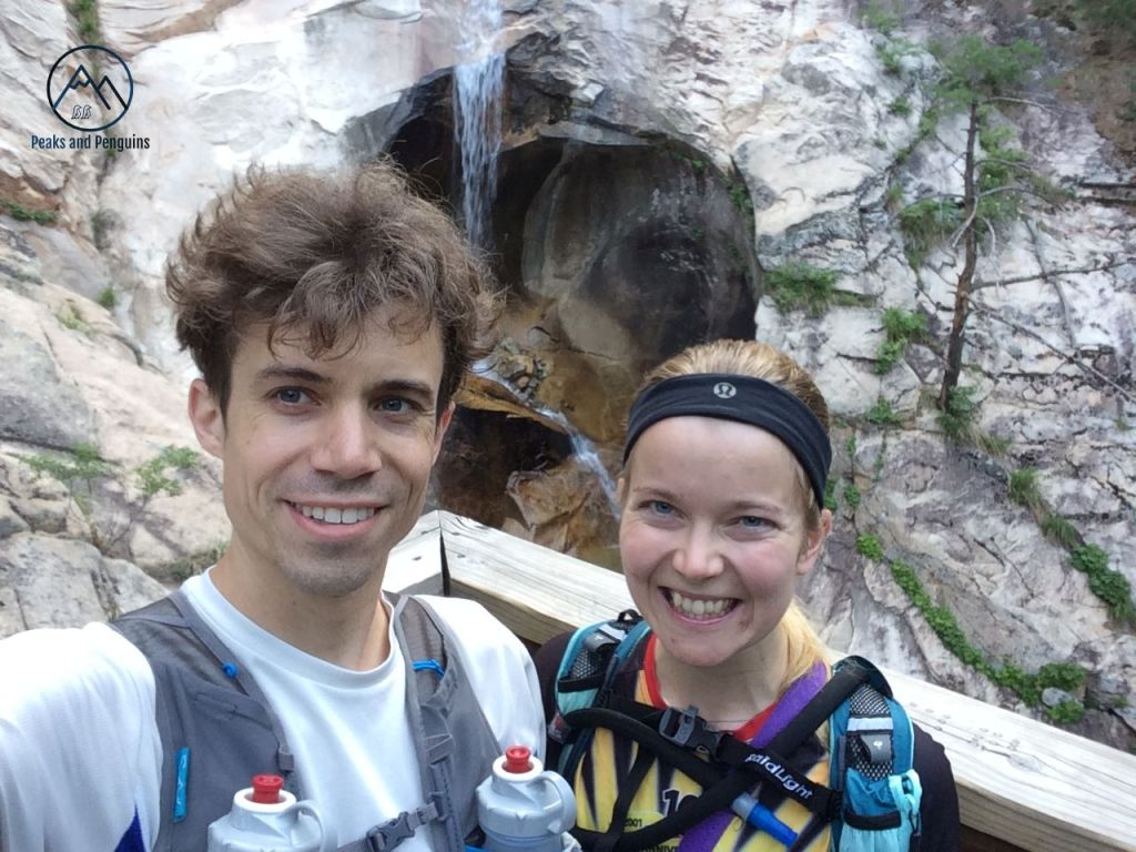 An image of the author and her husband standing in front of a waterfall. There is a wooden railing immediately behind their two smiling faces, and beyond that, water splashes down from a flat grey rock into a tan-colored rock cave.