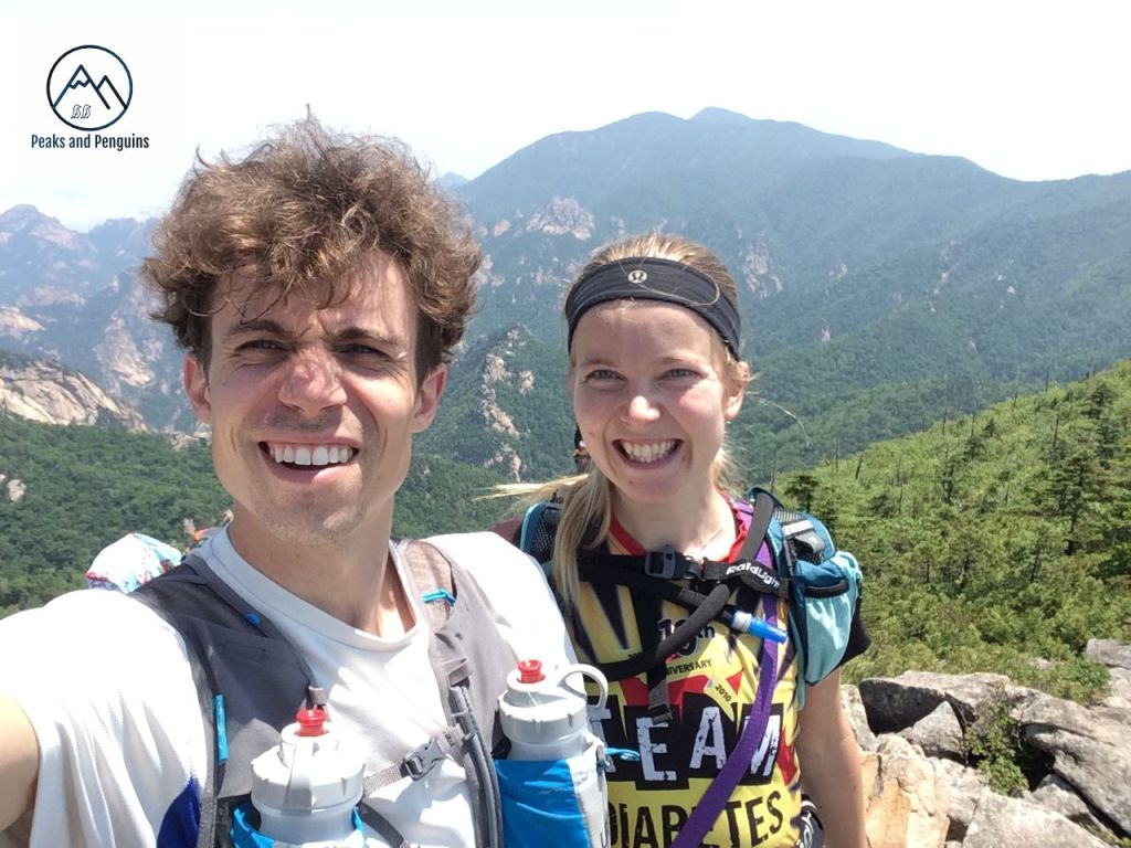 An image of the author and her husband on Gwittaegicheongbong. They are squinting into the bright sun and standing atop some of the big boulders on the summit. Beyond them are more wonderful views of the mountains in green and grey.