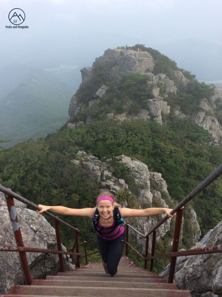 An image of the author ascending the steep, thrilling steps up to peak number two. She is gripping the brown handrails on either side of the staircase, and her face is lit up with a smile. Behind her, the first rocky peak is visible above the forest.