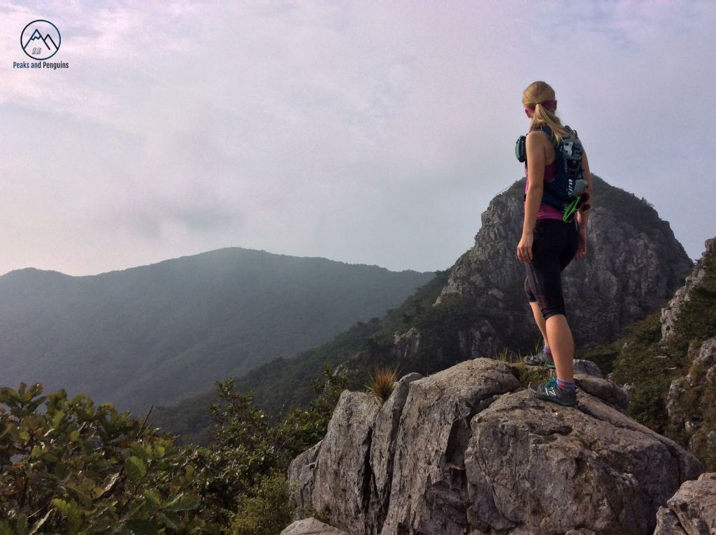An image of the author standing on some boulders to take in a beautiful view. Her back is to the camera, and she is looking at a huge rocky peak to her right. A long ridge begins behind that rocky peak and extends out of the frame to the left.