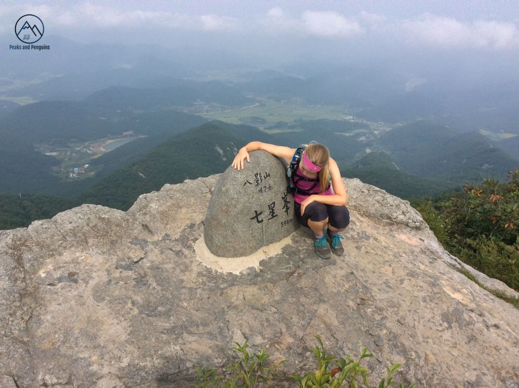An image of the author and the seventh peak of Paryeongsan. This is a great image for showing the scenery. The bottom half of the image shows the sloping seventh peak in the mountain's grey and tan rock. The summit stele is shorter and wider than the previous ones, and the author is crouched beside it. She has one arm draped over it and appears to be examining it. The upper half of the photo is a mosaic of bright rice fields and dark mountain slopes. The shoreline is just barely visible in mist. There top of the photo is lined with a row of white clouds.