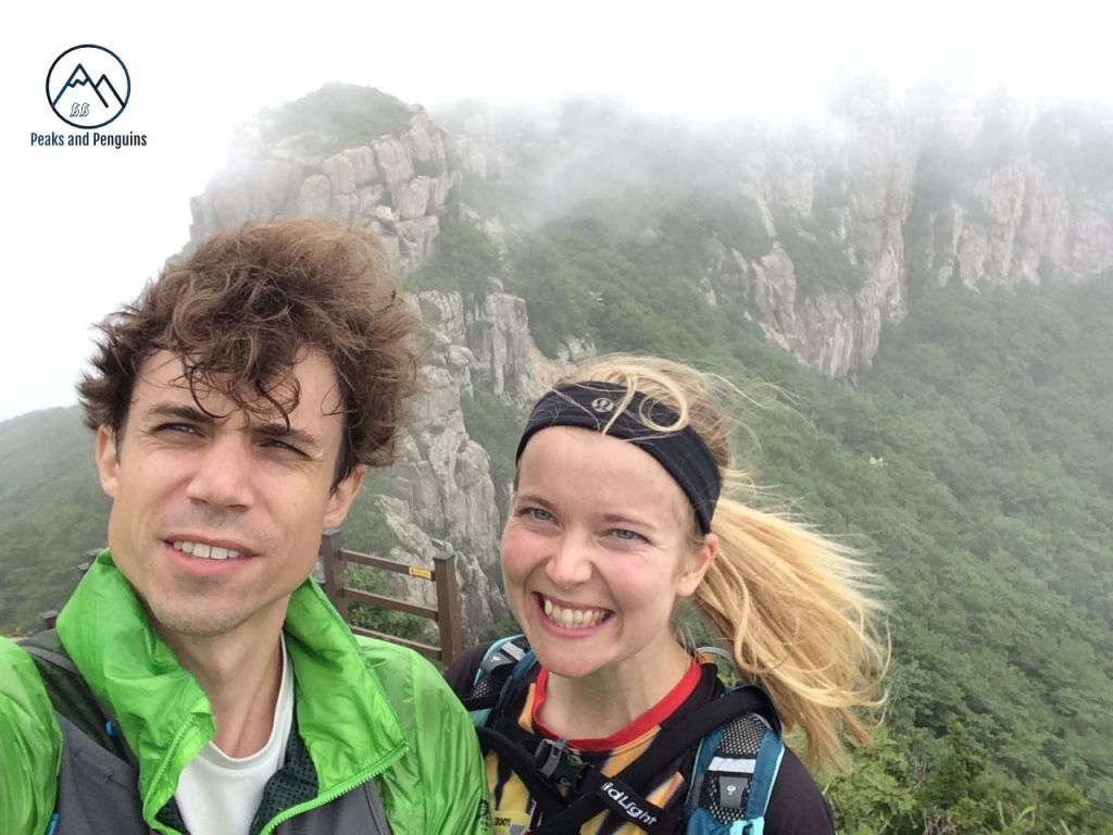 An image of the author and her husband in front of the rugged spine of Duryunsan Provincial Park. It's a windy day, and their hair is wild. Jagged grey rocks rise up from an emerald forest into the misty sky behind them.