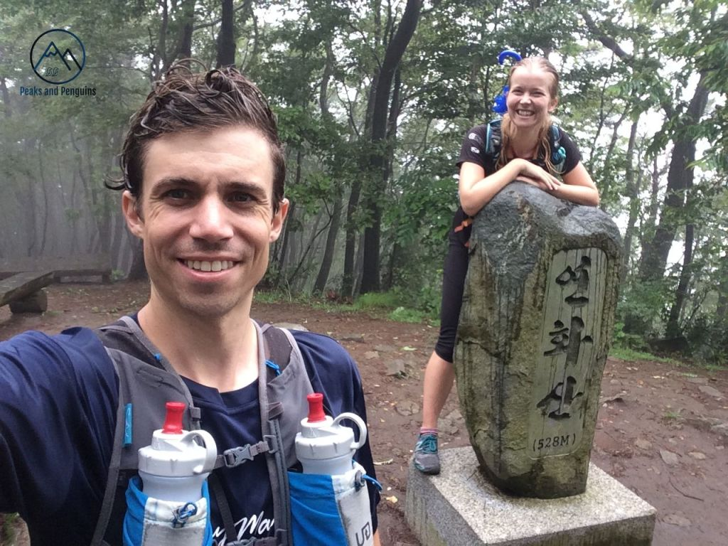 An image of the author and her husband. As usual, he stands closest to the lens. His hair and t-shirt are wet from the rain, and he's wearing a running vest. The author stands behind him, leaning with both forearms on the Yeonhwasan summit stele. Tall trees surround the summit area, mist woven in between their trunks.