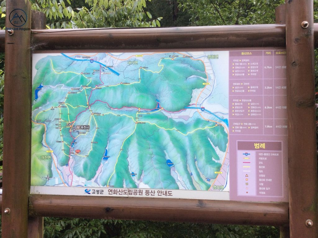 An image showing a signboard and map in Yeonhwasan Provincial park. Trails are indicated with yellow and red lines. Peaks and temples are also marked on this map, which has a simple, illustrated, green background.