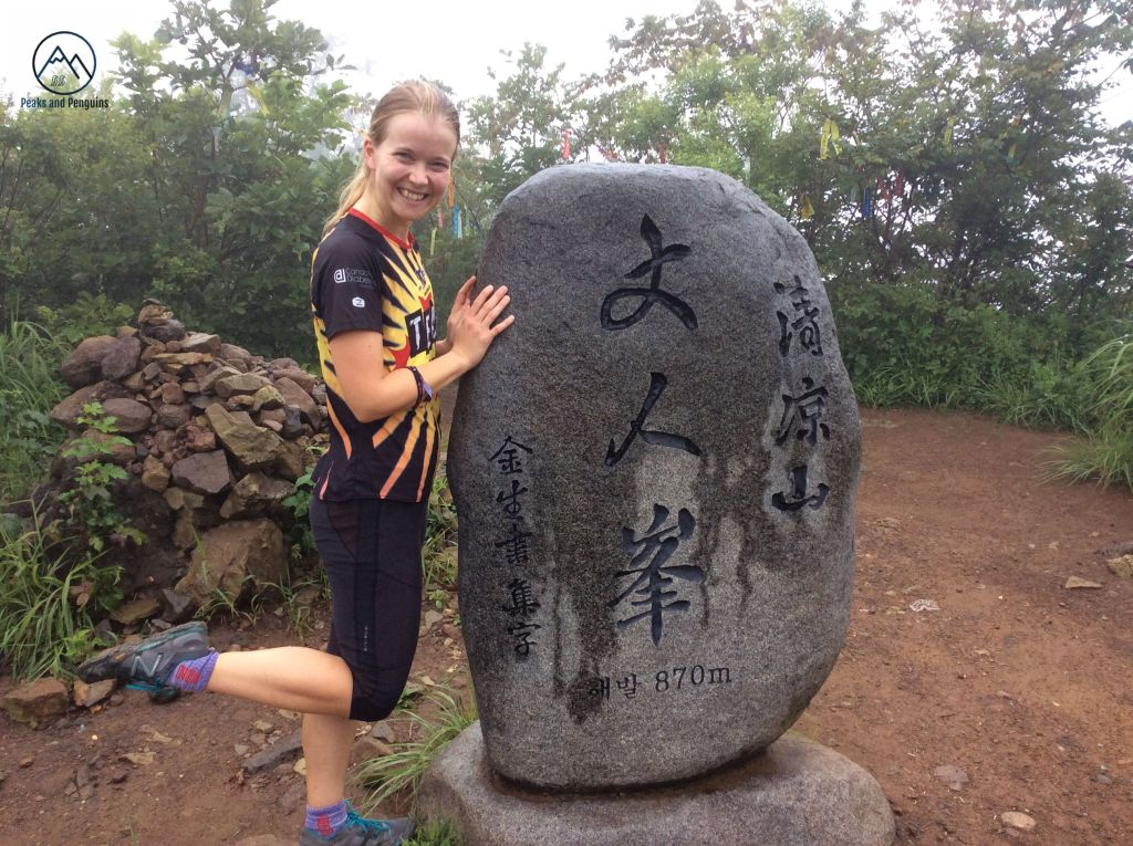 An image of the author posing with the damp summit stele of 870 meter Cheonginbong. The stele is a large, oblong rock inscribed with Chinese characters, and it is darker grey on top from the rain. The author is standing with both hands resting on it, one foot kicked up. Behind the stele is a small flat patch of bare earth, ringed by trees festooned in colorful hiking ribbons.