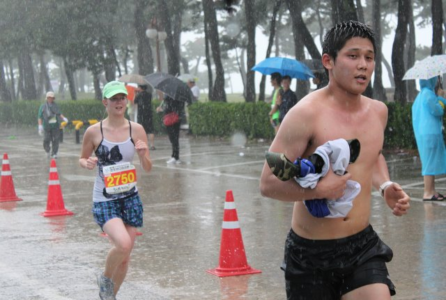 An image of the author running the Gyeongpo Beach 10k in 2011. Actually, a shirtless Korean man dominates the front right of the image, and the author is a smaller figure behind and to the left. She is wearing a green hat, and has a race bib pinned to her tanktop. The streets are flooded and the heavy raindrops are visible in the picture.