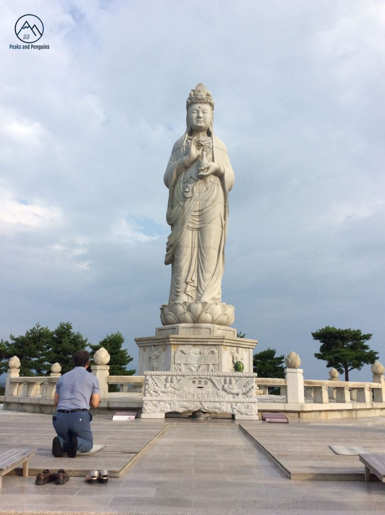 An image of a man kneeling at the foot of a large, white statue. This goddess of mercy statue is set upon the highest slope of the hills that form Naksan Provincial Park, and can be seen from miles away.