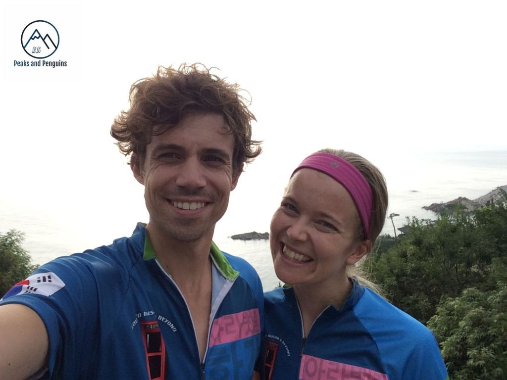 An image of the author and her husband. They are wearing matching bicycle jerseys. They face the camera; their backdrop the waters and islands of the east sea.