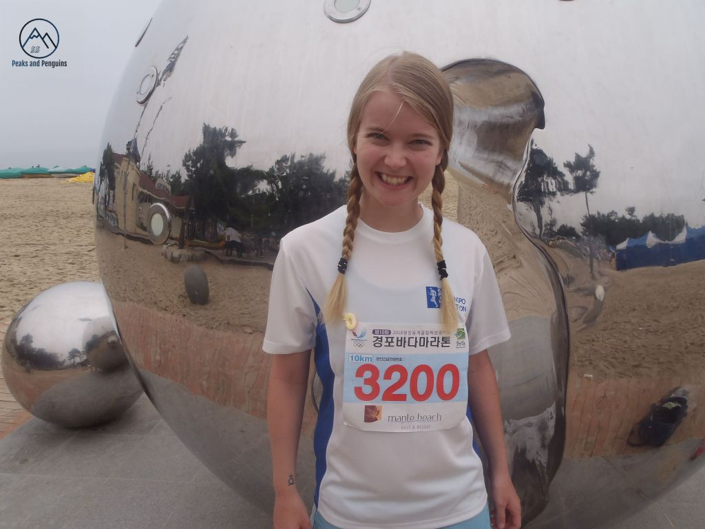 In this image, the author poses in her race attire in front of a giant, mirrored orb. Her hair is plaited and she wears bib number 3200.