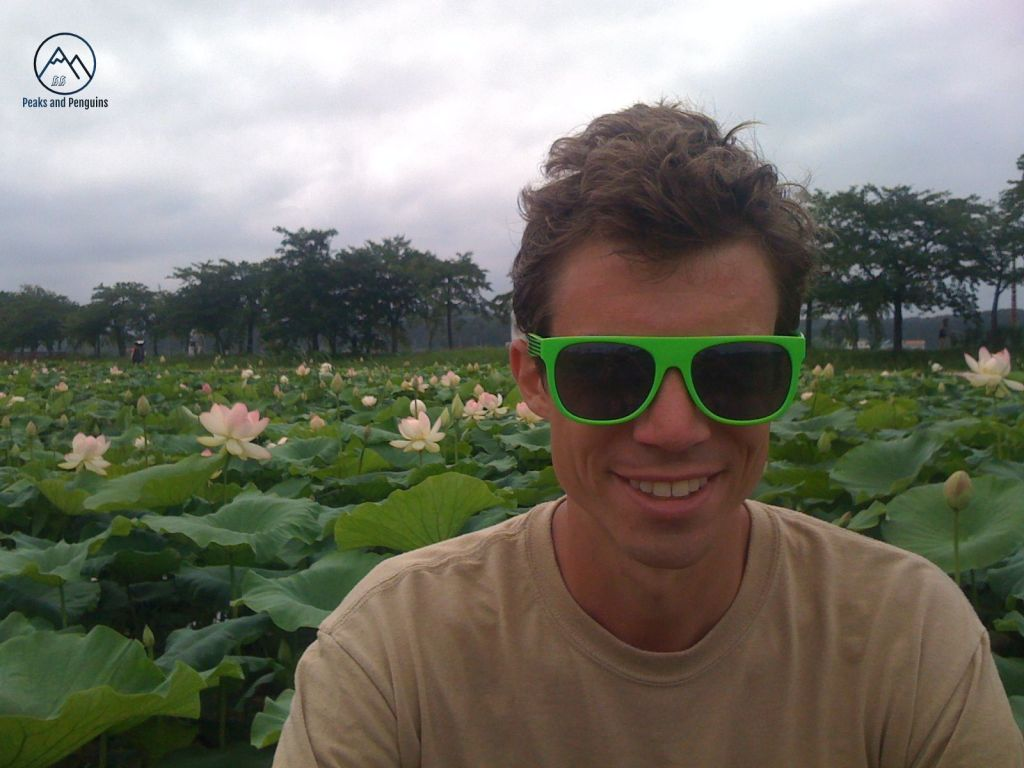 A portrait of the author's husband. His face is tanned, his brown hair blown a bit in the wind, and he's wearing bright green sunglasses. He's giving the camera a wide, genuine smile. Behind him is a field of the broad green leaves of lotus plans and their large pink blooms.