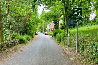 """""""Quiet Lane"""" sign on a rural lane at Mill Brow near Marple Bridge. The sign shows a car, cyclist, horse and pedestrians, denoting a hierarchy of patience amongst users."""