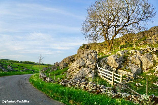 Limestone protrudes dramatically from the sides of Long Dale below a tumulus.