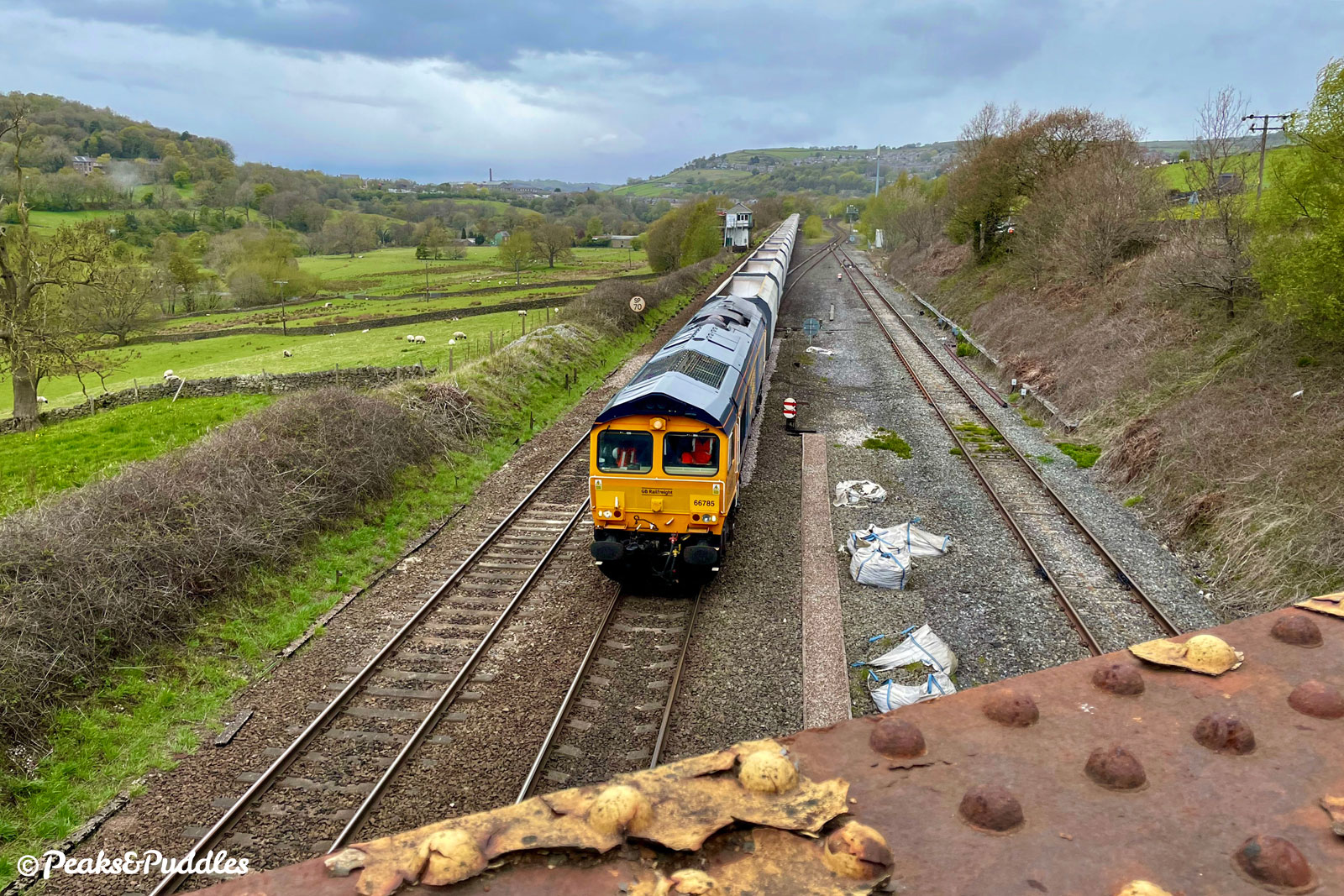A Class 66 freight locomotive pulls empty limestone wagons back into the Peak District at New Mills South Junction.