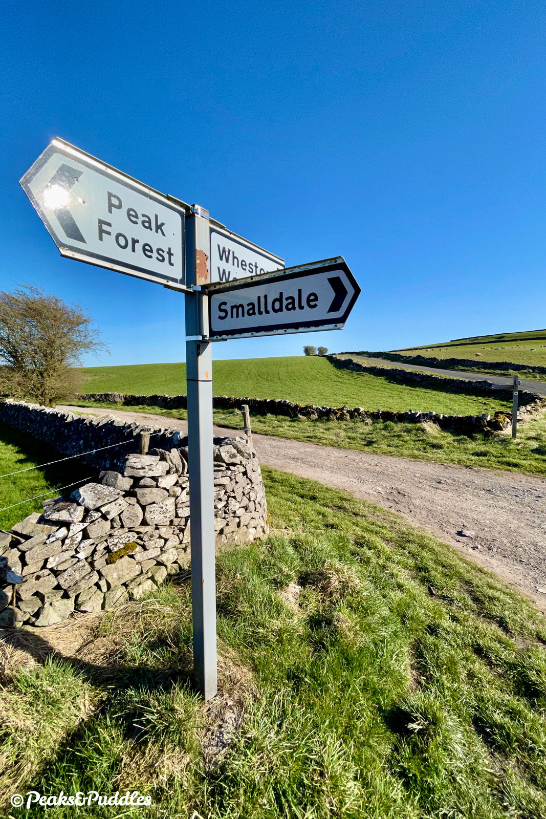 Signposts point right to Smalldale. The road onwards to Wheston and Tideswell is also ideal for cycling.