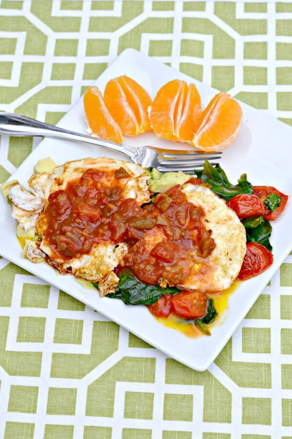 Whole30 compliant eggs fried in ghee over sauteed spinach and tomatoes and avocado topped with salsa.