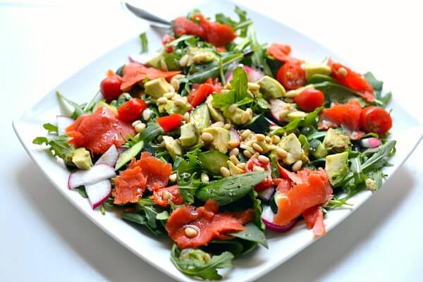 Whole30 approved salad with spinach, arugula, cucumbers, tomatoes, avocado, pine nuts and smoked salmon.