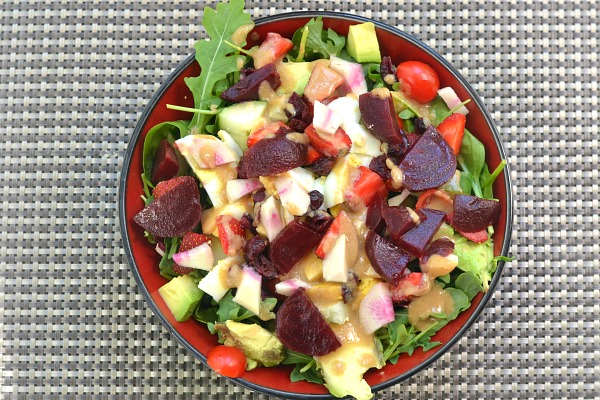 Lunch salad with fruits, veggies, nuts and tahini dressing