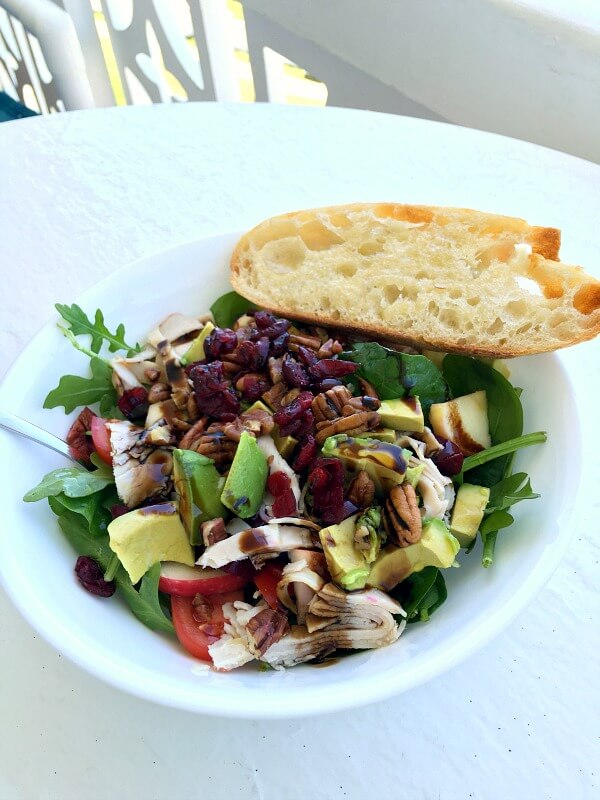 Salad with Spinach, arugula, tomatoes, deli turkey, avocado, apples, pecans, cranberries and a buttered sourdough toast.