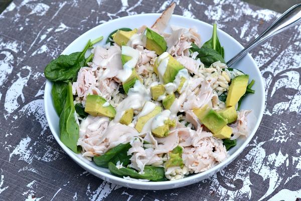 Salad with spinach, lemon pine nut orzo, deli turkey, avocado and tahini dressing