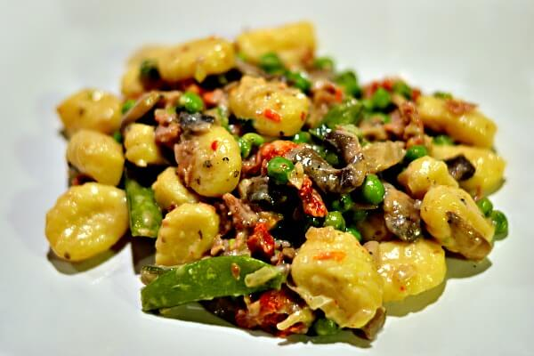 Gnocchi with sauteed mushrooms, prosciutto and peas