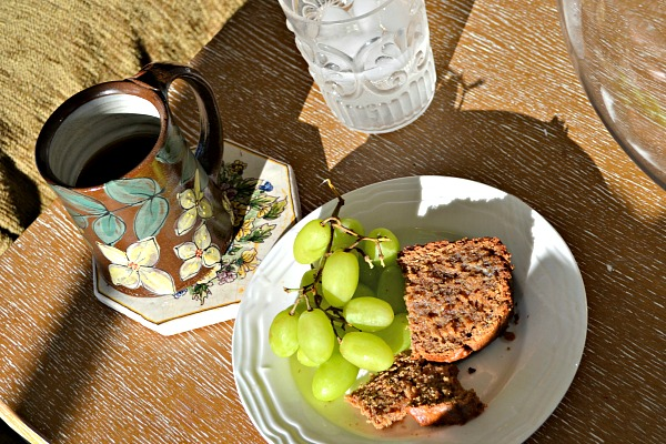 Coconut peanut butter banana bread topped with butter along with some grapes, coffee and water