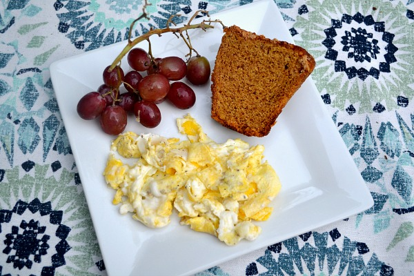 Two scrambled eggs, grapes and half of a pumpkin muffin