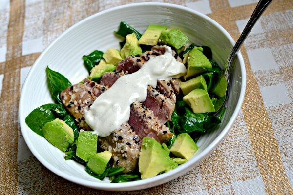 Sesame seared tuna over sauteed spinach with avocado and wasabi aioli.