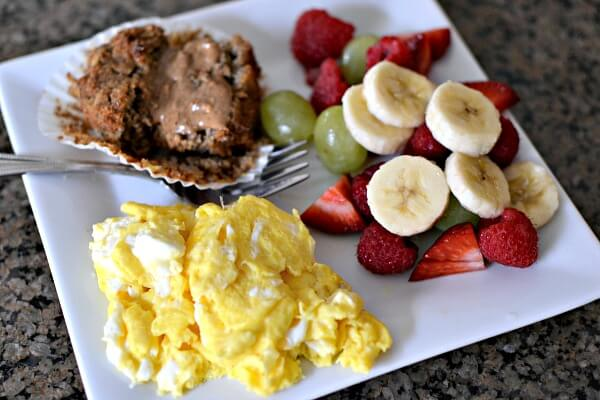 Scrambled eggs, fruit and a paleo banana bread muffin with almond butter.