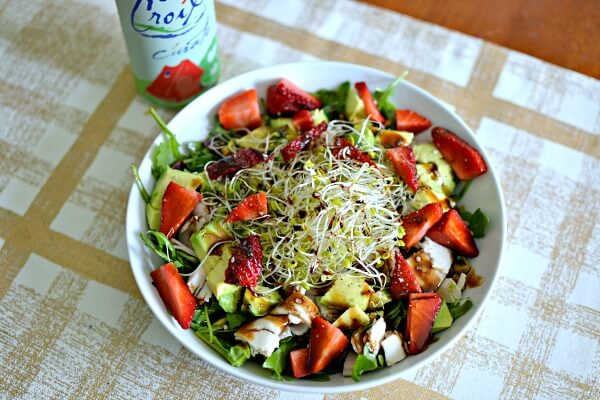 Salad with arugula, avocado, turkey, strawberries, sprouts, dried cranberries, pistachios and olive oil + balsamic.