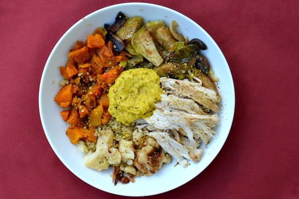 Quino lunch bowl with cauliflower, butternut squash, brussels and chicken. Topped with Thai Coconut Curry hummus.