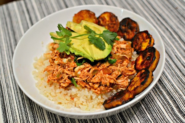 Slow cooker salsa chicken over cauliflower rice. Topped with cilantro and avocado and served with pan-fried plantains.