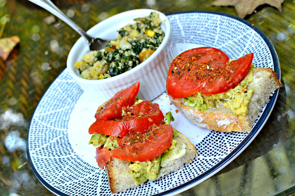 open faced smashed avocado and tomato sandwiches with kale and quinoa salad on the side