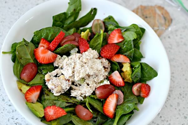 Spinach salad with avocado, grapes, strawberries and chicken salad.