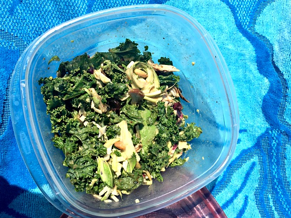 Kale salad with chicken, avocado, nuts and seeds.