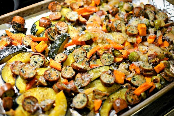 One pan roasted dinner with acorn squash, carrots, sweet potatoes, brussels spouts, Vidalia onion and spinach feta chicken sausage.