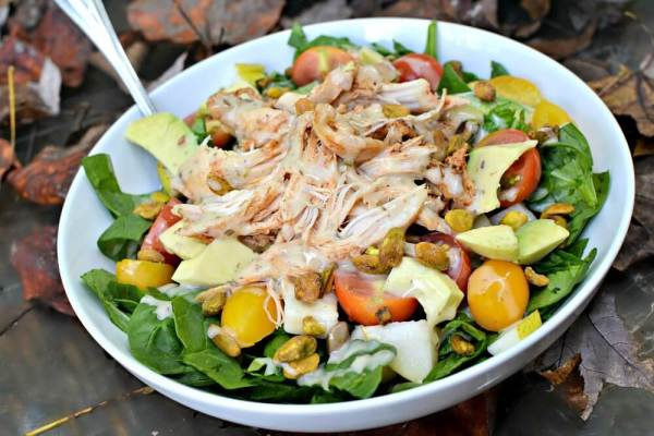Salad with chopped spinach, cherry tomatoes, pistachios, pears, avocado, shredded BBQ chicken and Primal Kitchen avocado oil ranch.