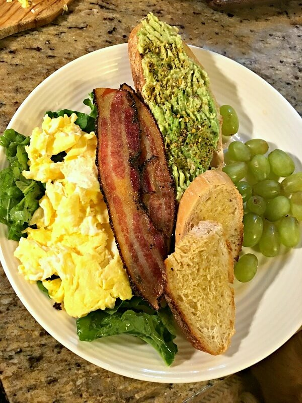 Scrambled eggs over arugula, bacon, avocado and buttered toast and grapes