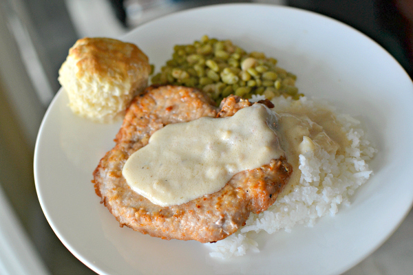 Pan-fried pork cube stead with homemade gravy over rice with fresh peas