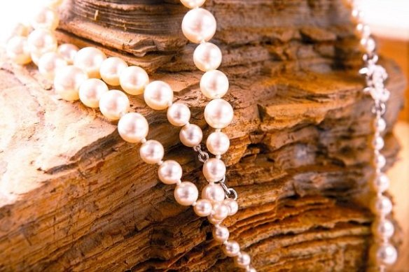 pearl pendant displayed on large rock