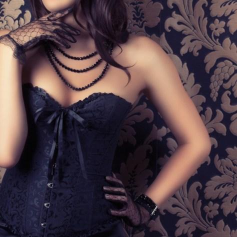 Frau mit Korsett und schwarzer Perlenkette