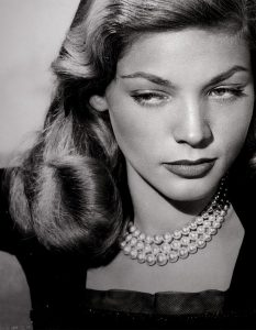 lauren bacall wearing triple strand pearl necklace